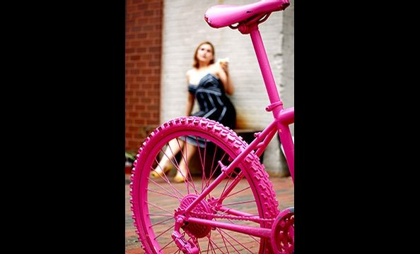 """Pop of Pink"" is a shot of a rehabbed bike outside Baked & Wired in Georgetown.  The photographer's roommate, Erin Hamilton—who can be seen in the background— suggested a day of shooting in DC.  To get this winning shot, the photographer had to lie in the"