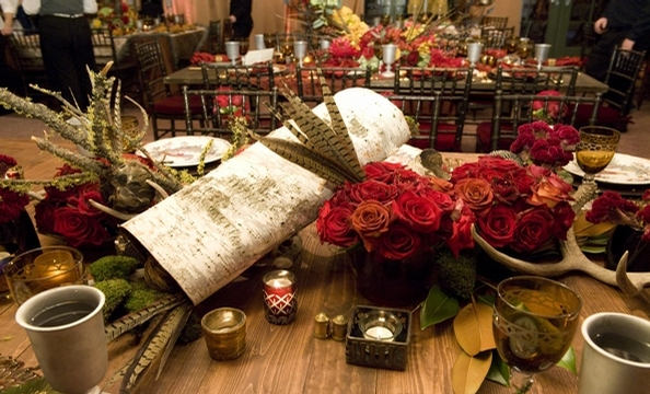 Birch logs, moss, pheasant feathers, moss-covered branches, deer antlers, and roses.