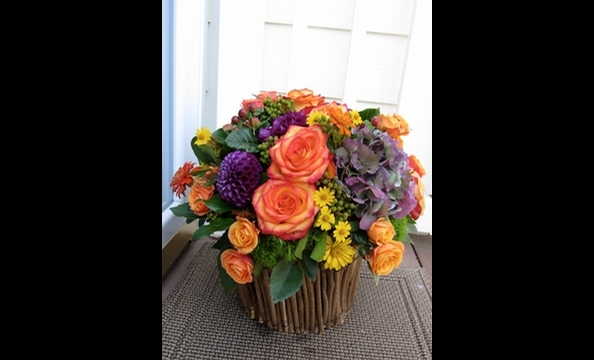Antique hydrangeas, dahlias, roses, spray roses, berzillia berries, wild daisies, and seasonal foliage in a twig basket.
