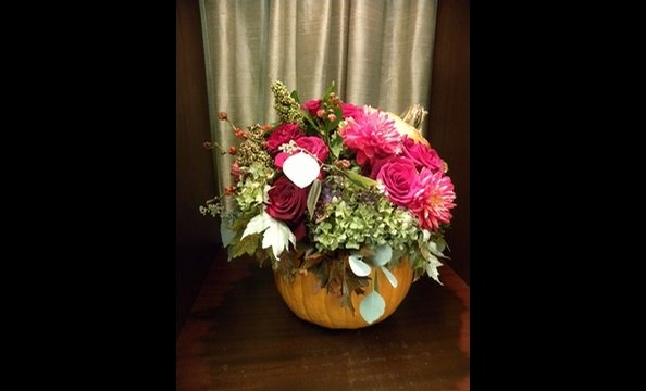 Hydrangeas, black magic roses, dahlias, amaranthus, oak leaves, and seeded eucalyptus arranged in a pumpkin.