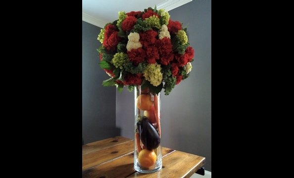 Hydrangeas, carnations, kale, and cauliflower in a vase filled with citrus fruits, carrots, and eggplant.