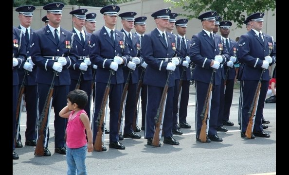 The contrast of the curious little girl and the all-business Honor Guard is striking.