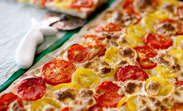 At G Street Food in downtown DC, bread guru Mark Furstenberg crafts airy Roman-style squares of pizza topped with tomatoes.