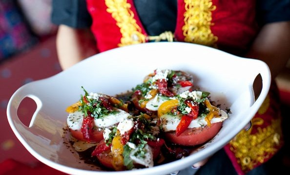 Alexandria Afghan restaurant Maizbon puts a vibrant twist on a tomato salad, with mozzarella, feta, roasted peppers, and herbs.