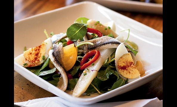 Traditional Spanish ingredients such as boquerones and roasted peppers accent an arugula salad at Estadio.