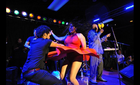 The energy of Arlington's Salsa Room comes alive in this vibrant picture taken at an Oscar D'Leon concert in April.  While performing, the legendary Venezuelan singer (holding maracas on the right) invited fans onstage to dance.  Photographer Jon Trevino,
