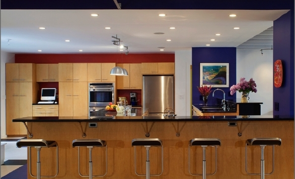 Bold paint colors and minimalist furniture and appliances give the kitchen an uncluttered look.