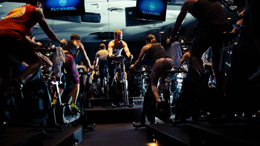 DC gyms fitness-tracking. Flywheel classes are set up stadium-style with screens at the front, which display riders' Torqboard statistics. Image courtesy of Flywheel Sports.