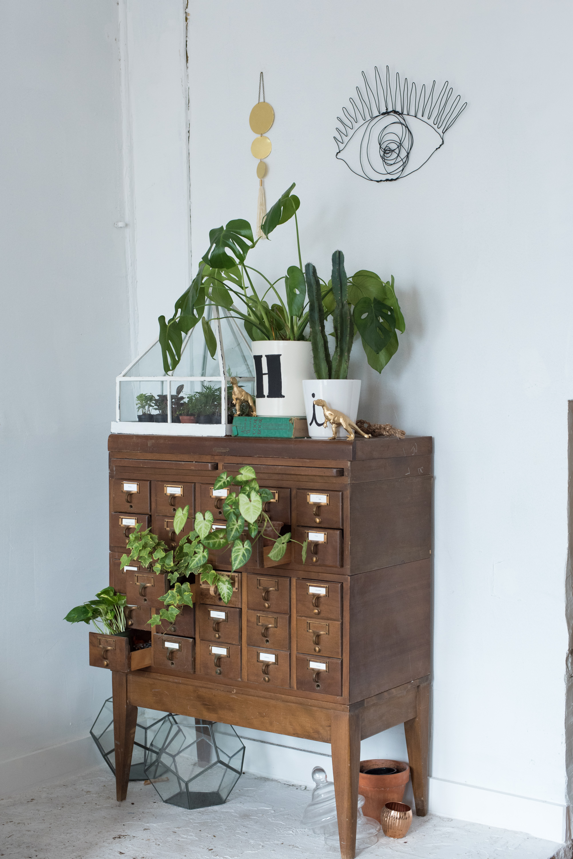 Lettered plant pots greet visitors on top of a card-catalog-cum-greenery-dispenser.
