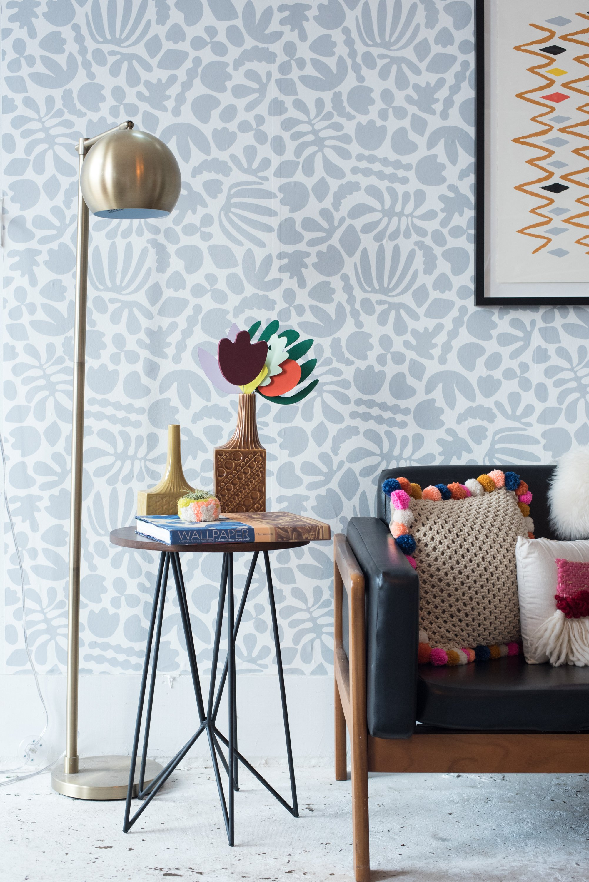 Zaremba's Matisse-inspired wallpaper forms a lively backdrop for the leather sofa and pom pom pillows.