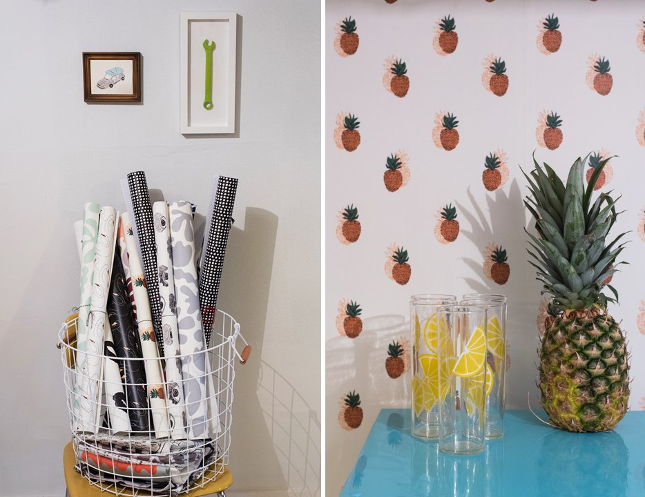 Sample rolls of Zaremba's whimsical wallpapers; the pineapple wallpaper turns a table and mini-fridge into a kitchen alcove.