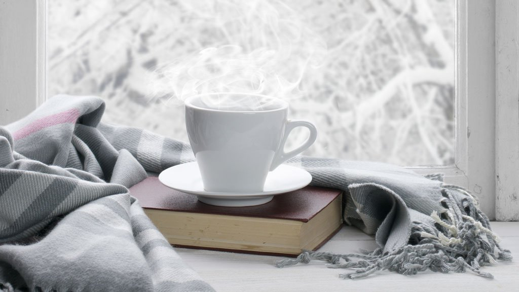 Cup of coffee on a book by the window.