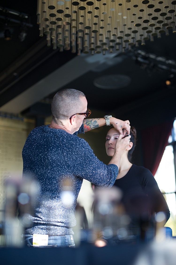 Makeup artist Carl Ray applies the finishing touches to a model before the runway show.