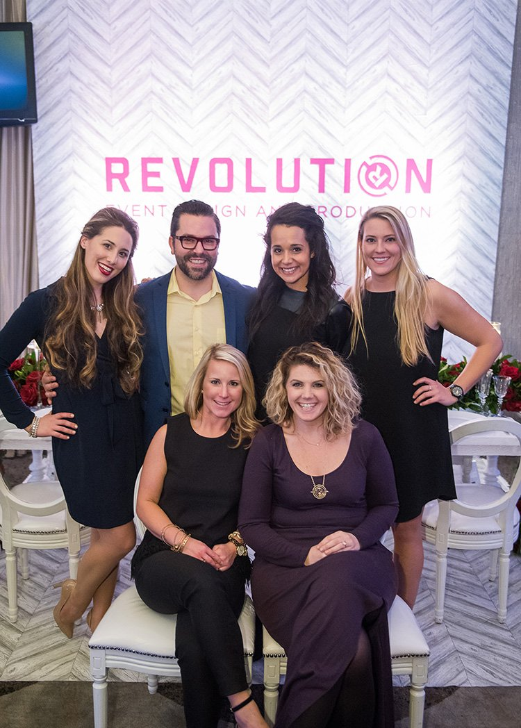 Hannah Cohen, Danny Tippett, Renee Diodonet, Olivia Brown, Caroline Clauss, and Katie Kirby from Revolution Events pose in front of their booth.