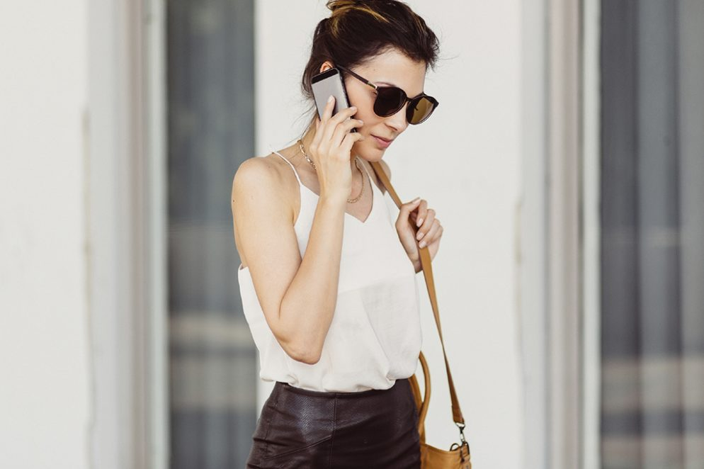 Business woman with mobile phone and bag on shoulder.