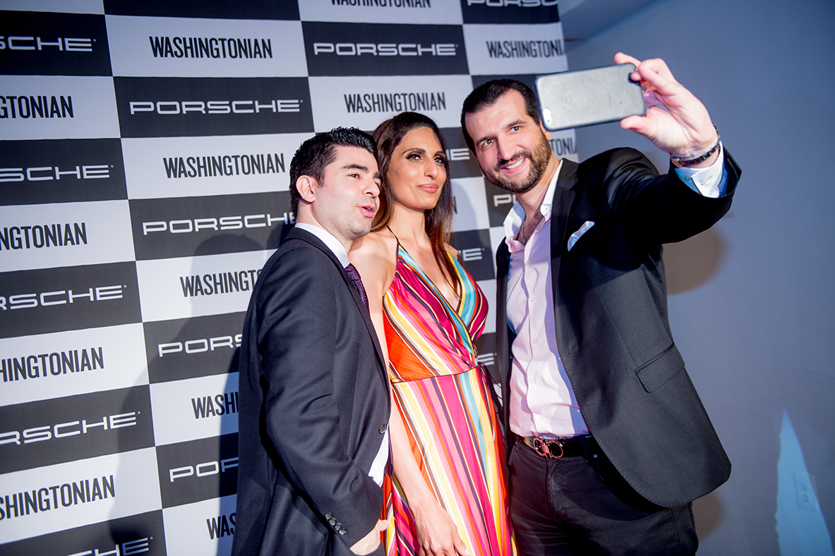 Guests pose for a selfie in front of the Porsche and Washingtonian step and repeat.