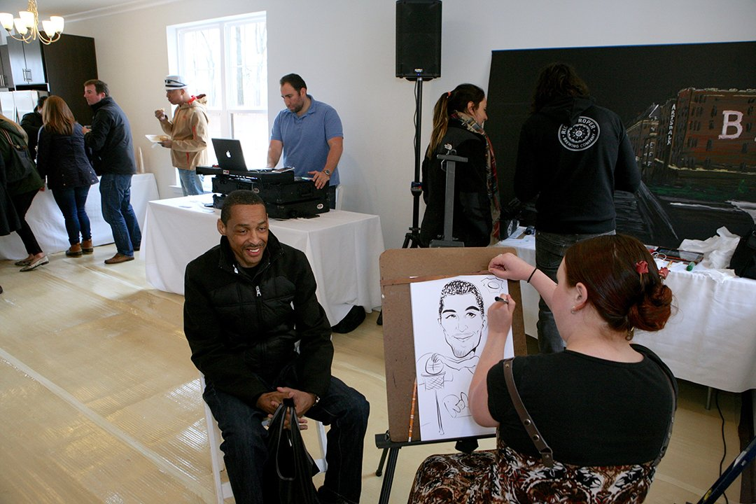 Robert Horton poses for a caricature drawing at the grand opening event.