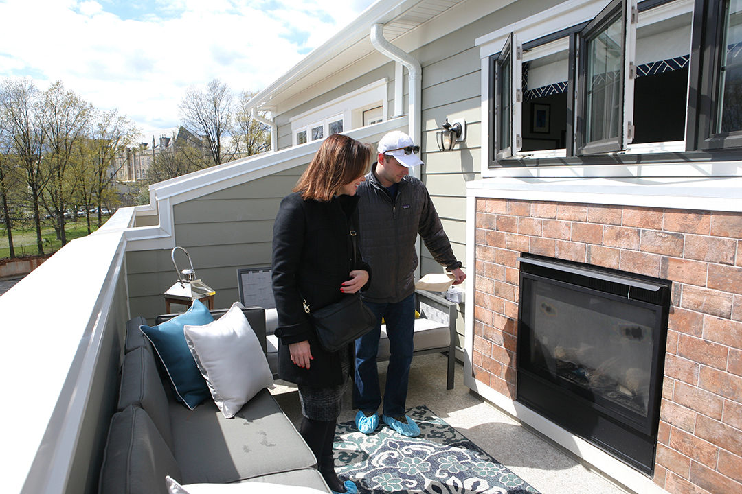 Kim Earls and Andrew Bolton admire the indoor / outdoor fireplace on the rooftop terrace.