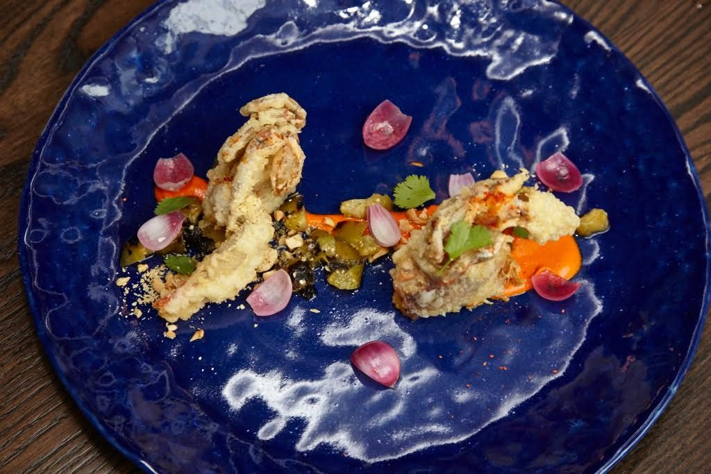 Chef Daniel Perron makes creative plates, such as this crispy soft-shell crab sauced with spicy peanut romesco.