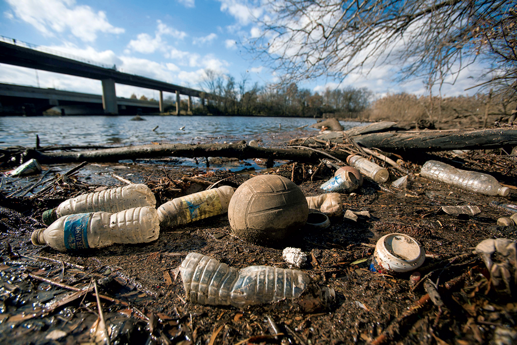 Plastic bottles and other debris float on the banks of the river. Photograph by EPA/Alamy.