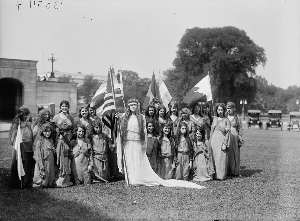 A woman in a Columbia costume with a group of dancers. Photograph via Harris & Ewing Collection (Library of Congress).