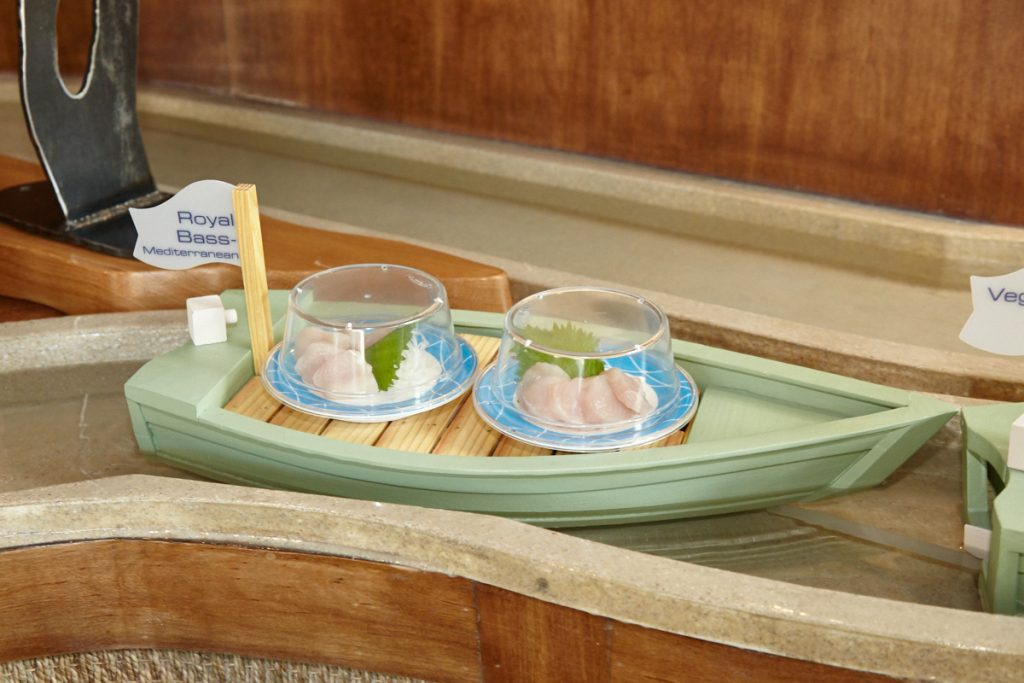 Small dishes like sushi rolls and sashimi float along on boats made by a local woodworker.
