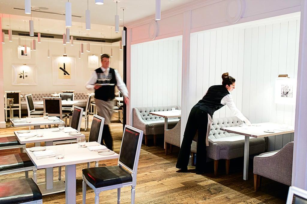 Kinship staffers prepare the Darryl Carter-designed dining room for service.