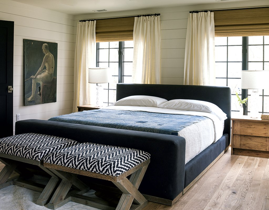 In one of the house's three master bedrooms (top), moody blues impart a nautical feel. For the bunkroom (below) Liess went more literal, with vintage aquatic posters lining the shiplap walls. Photograph by Helen Norman.