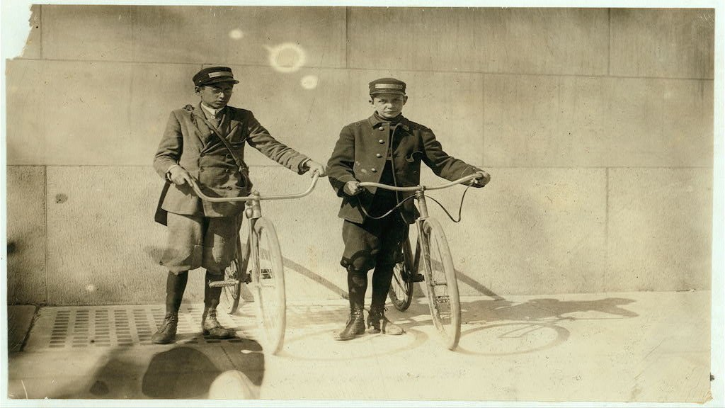 Bike messenger boys Earle Griffith and Eddie Tahoory working April of 1912. Photograph by Lewis Wickes Hine \ via Library of Congress