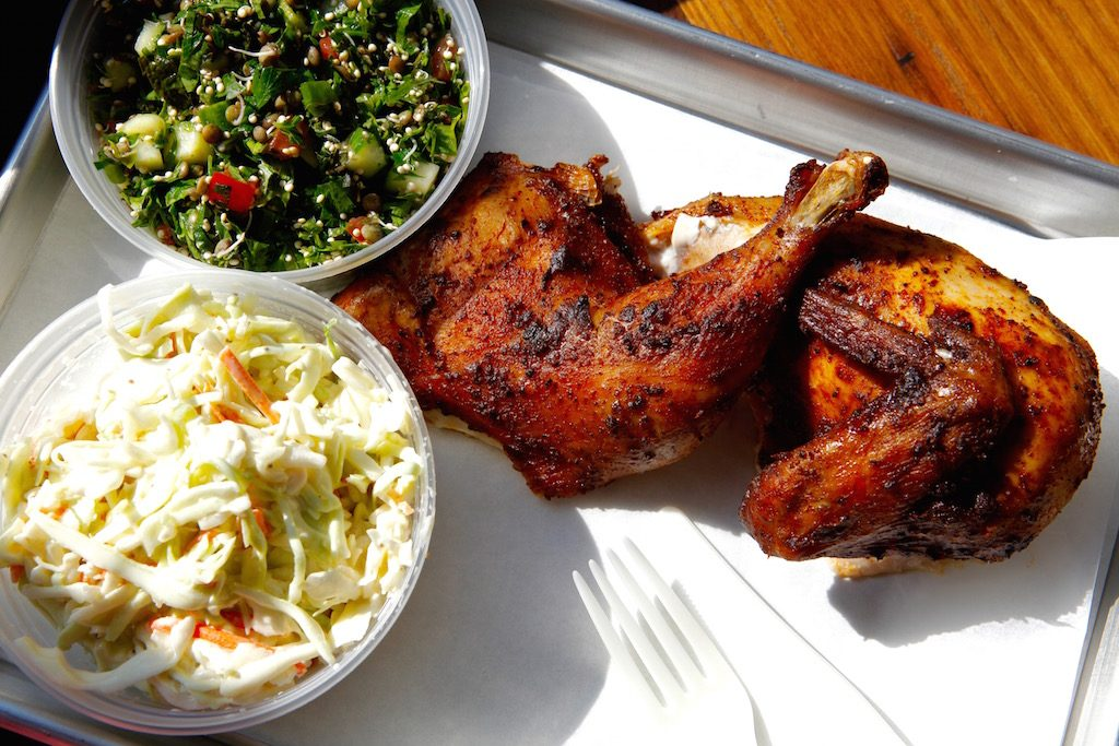 A platter of brined, smoked, and spiced chicken comes with a choice of two sides (here: slaw and sprouted tabouli).