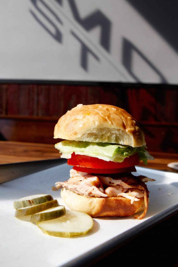 The Chicky Chick sandwich with pulled chicken and summer tomato on a homemade milk bread bun.