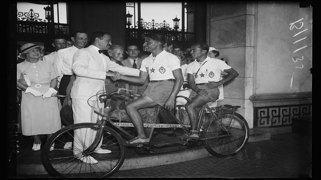 Dr. Loo S. Rowe of Pan-American Union greets Argentinian cyclists Victor Scarraffia (front) and Vincente Gregori (rear) in 1934 after they complete a 2 and a half year journey.