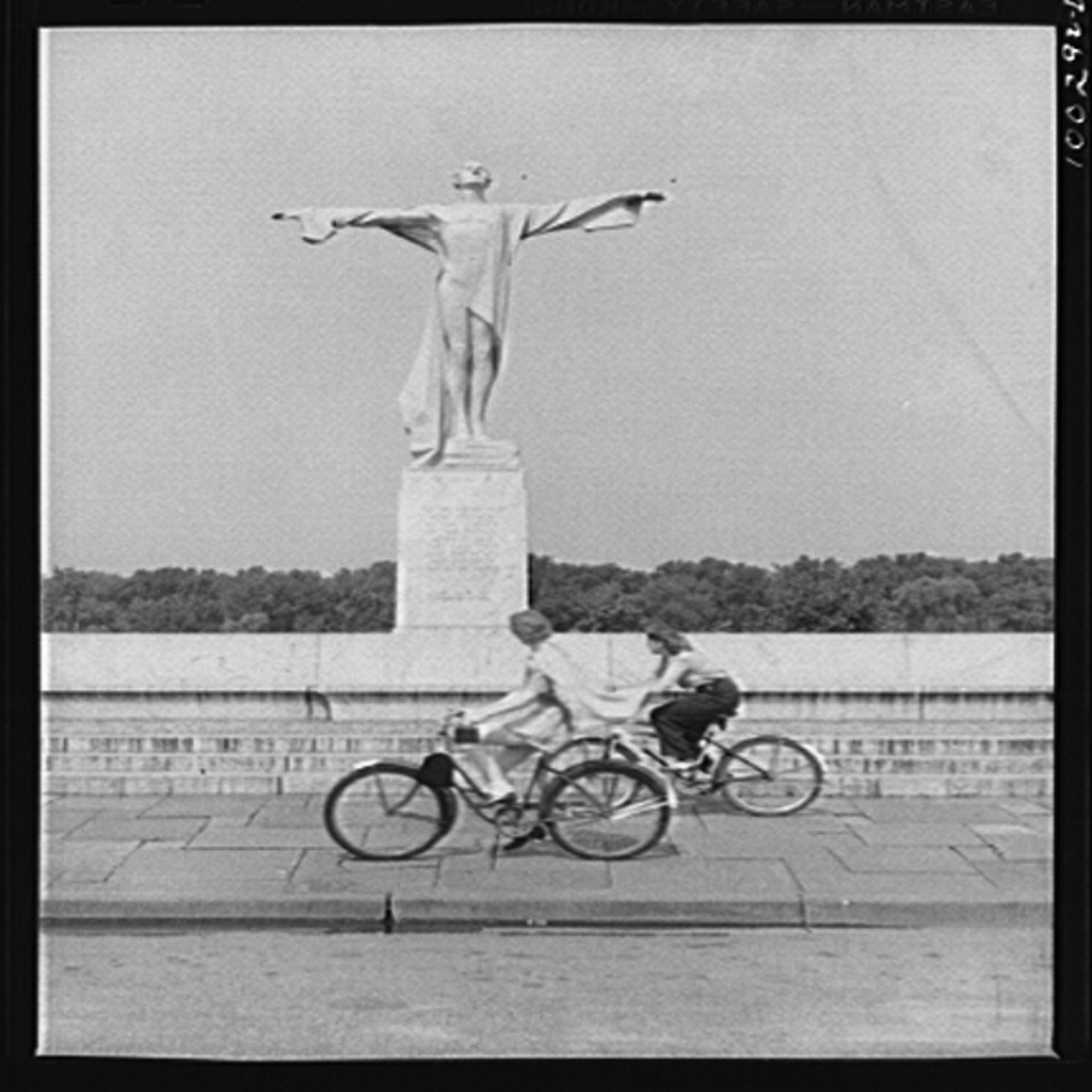 Bikers pass a statue in East Potomac Park erected in memory of the victims of the Titanic. Photograph by Marjory Collins