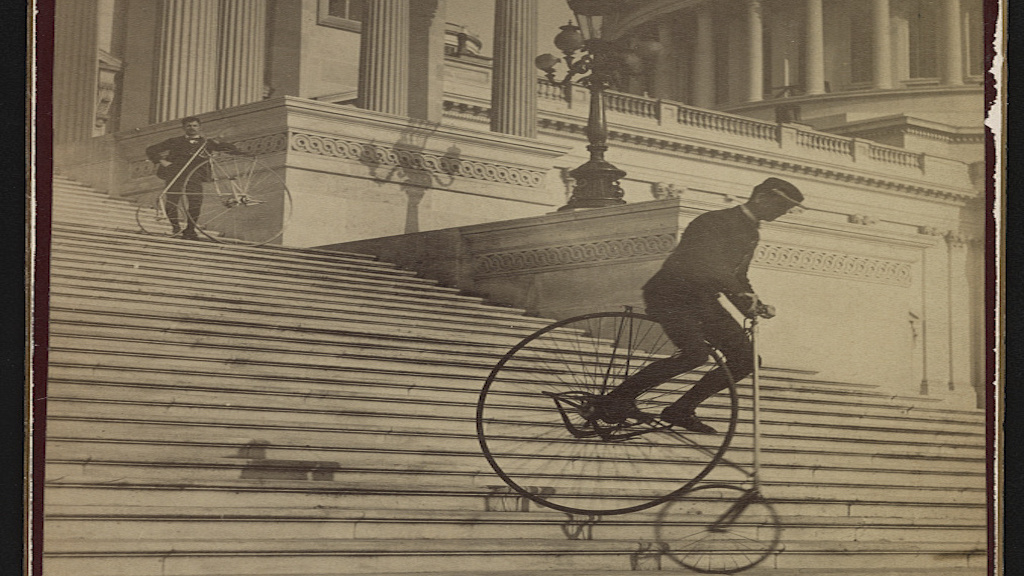 Man attempts to ride down the steps of the US Capitol Building Photograph by the Platt Brothers\ via Library of Congress.