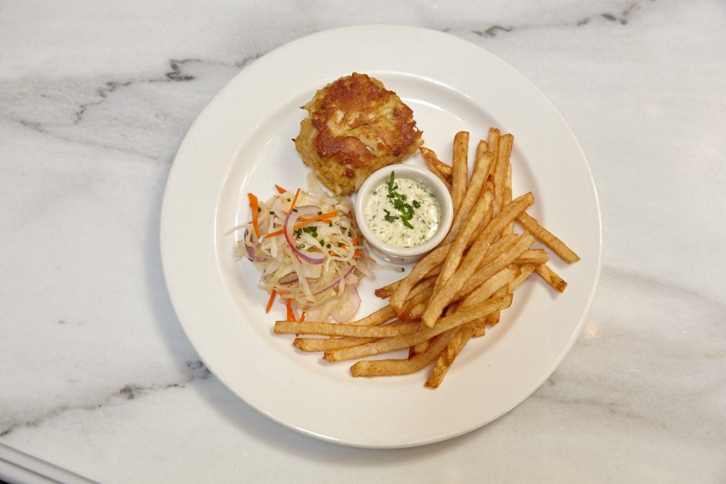 Cashion's crab cakes, a staple of Johnny's since opening in 1999. In order to make the dish wallet-friendly, Cashion serves one instead of two at the new restaurant, plus sides.