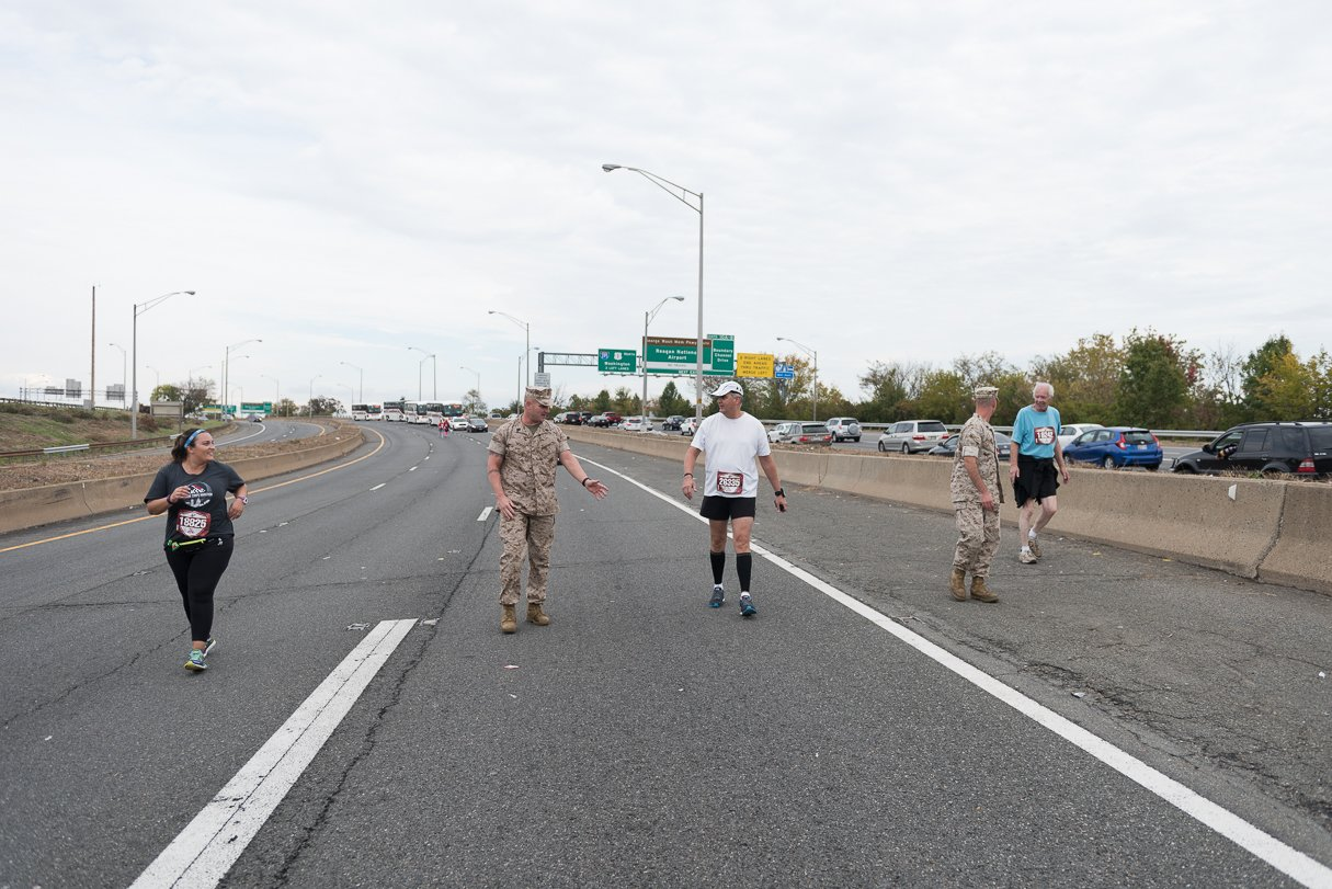 Marine Gunnery Sergeant Mark Bender is the guy who explained to runners gently, but firmly, their options for the rest of the afternoon: finishing along sidewalks after the roads open or riding the bus.