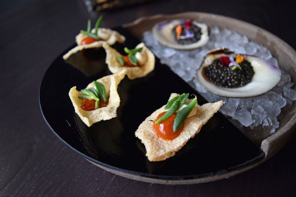 A meal begins with drinks and snacks, like these shrimp chips and sous-vide clams with caviar.