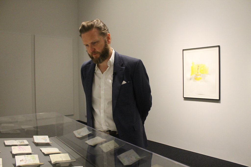Ragnar Kjartansson looking at his sketchbooks at the exhibition. Photo by Greta Weber.