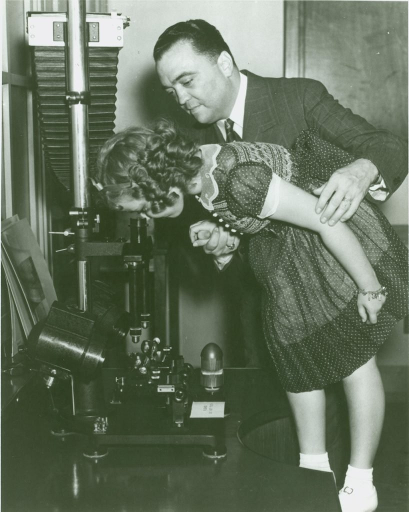 FBI Director J. Edgar Hoover showing actress Shirley Temple a microscope in the FBI's crime lab in 1938.