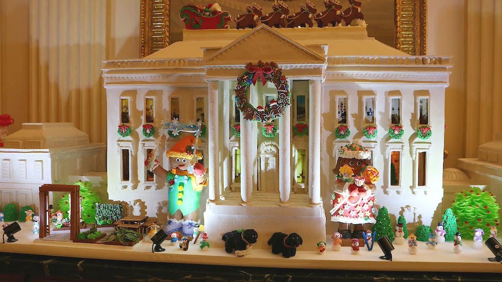 A mini White House made of gingerbread sits on the mantle of the State Dining Room.