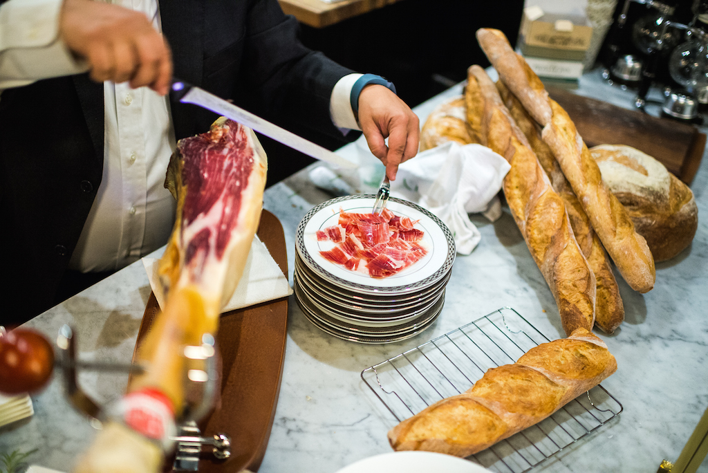 "Servers shave slices of prized ""jamon Iberico de Bellota"" alongside fresh bread."