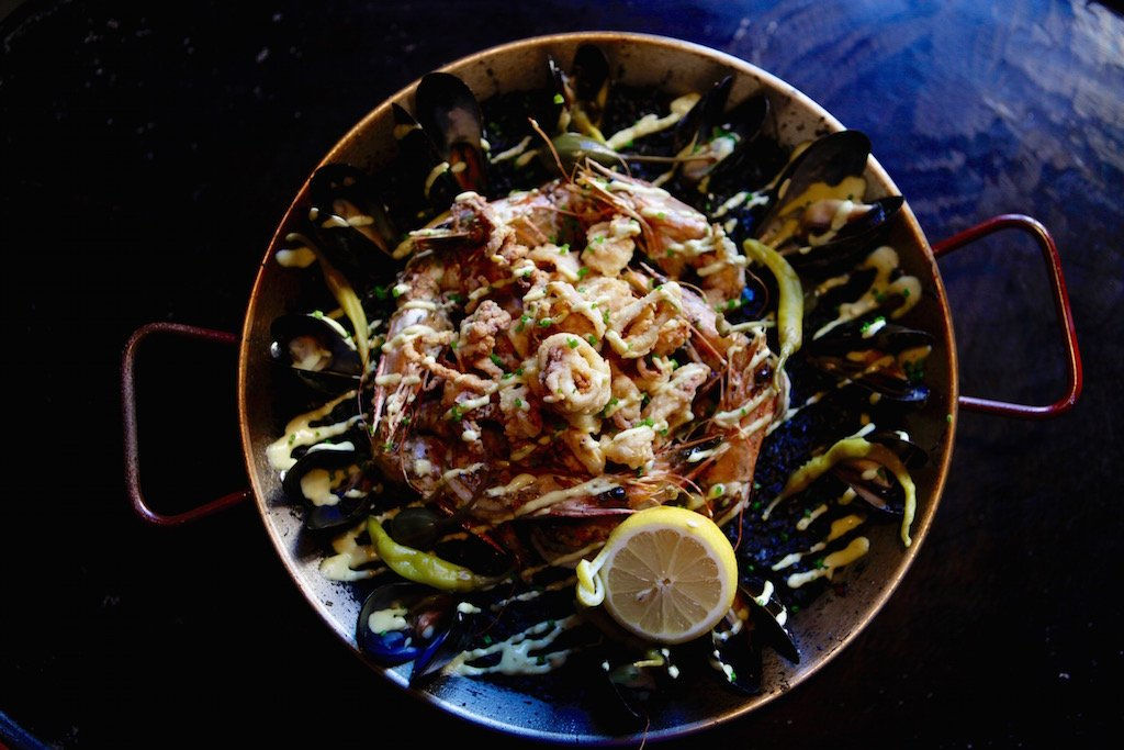 Three styles of paella are served by the pan, including this seafood variety.