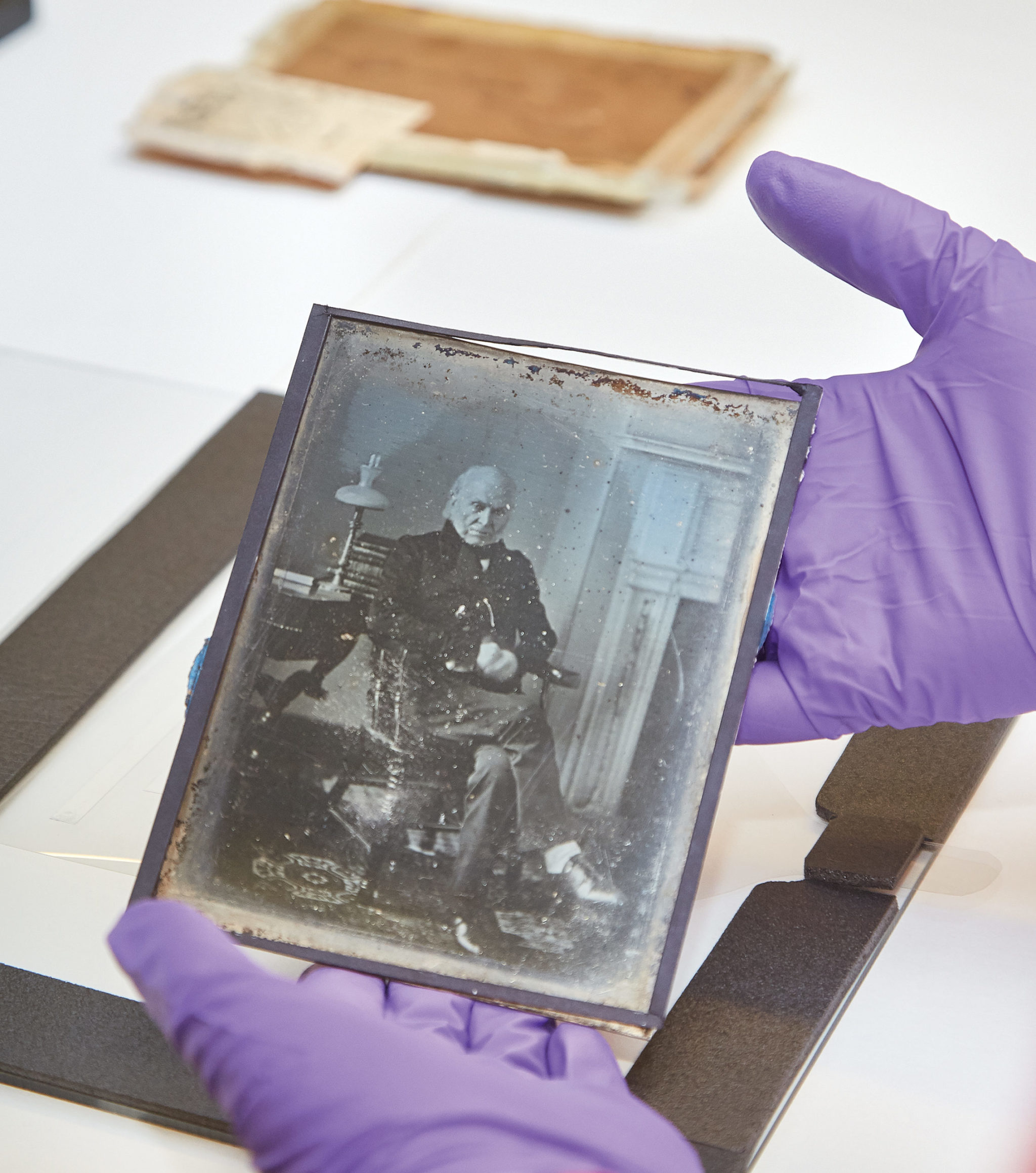 A museum conservator holds the 1843 Adams photograph. Photograph by Jeff Elkins.