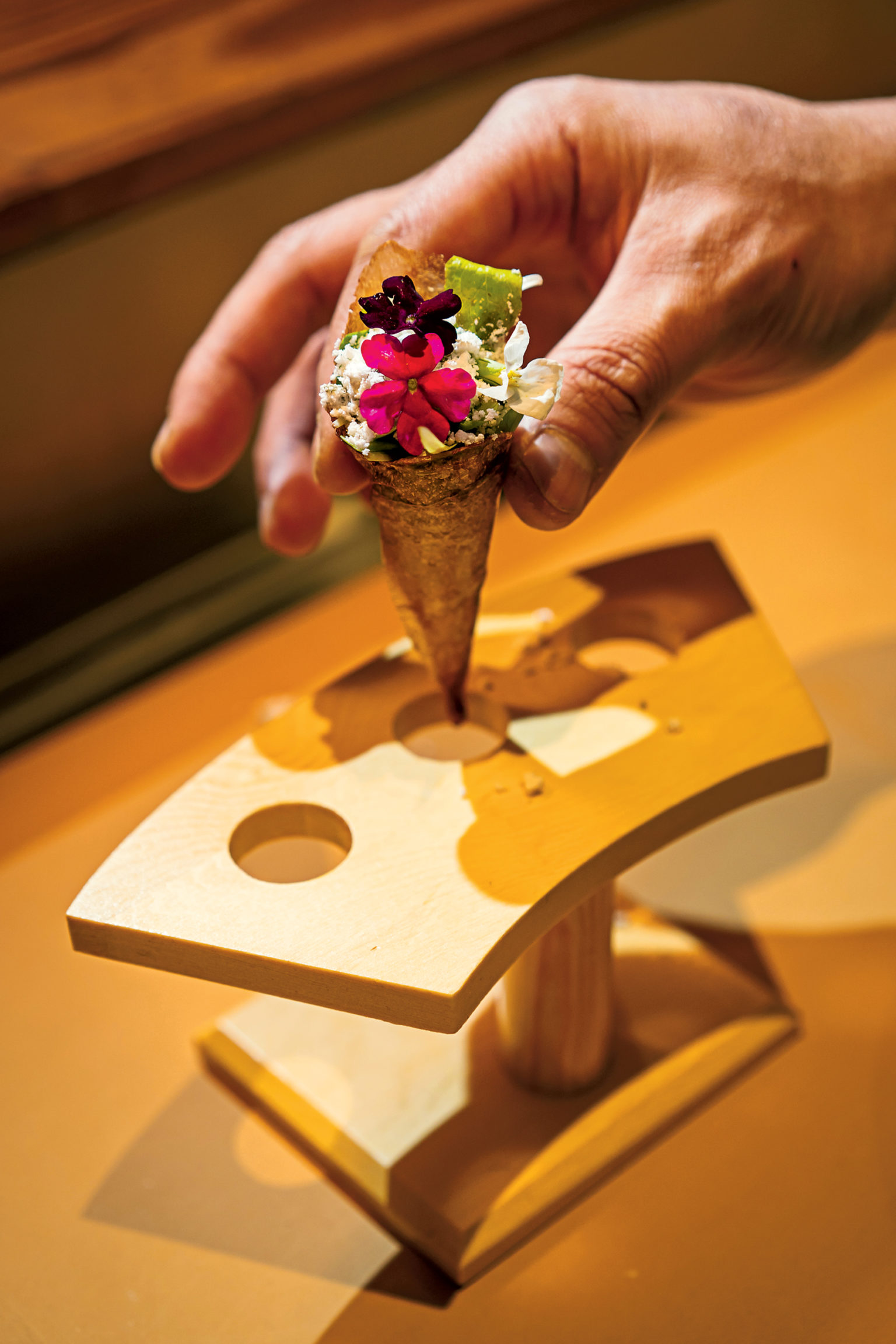 It takes a day to make delicate cones of potato starch, soy, and yuzu, which are used instead of nori for hand rolls stuffed with baby lettuce, orange powder, and edible flowers.
