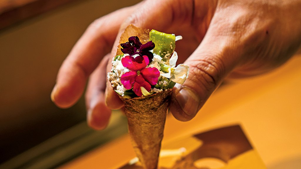 It takes a day to make delicate cones of potato starch, soy, and yuzu, which are used instead of nori for hand rolls stuffed with baby lettuce, orange powder, and edible flowers. Photograph by Scott Suchman.