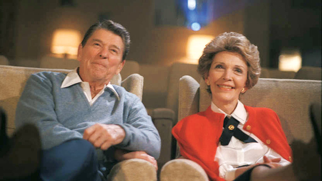 Ronald and Nancy Reagan watch a movie in the White House theatre.