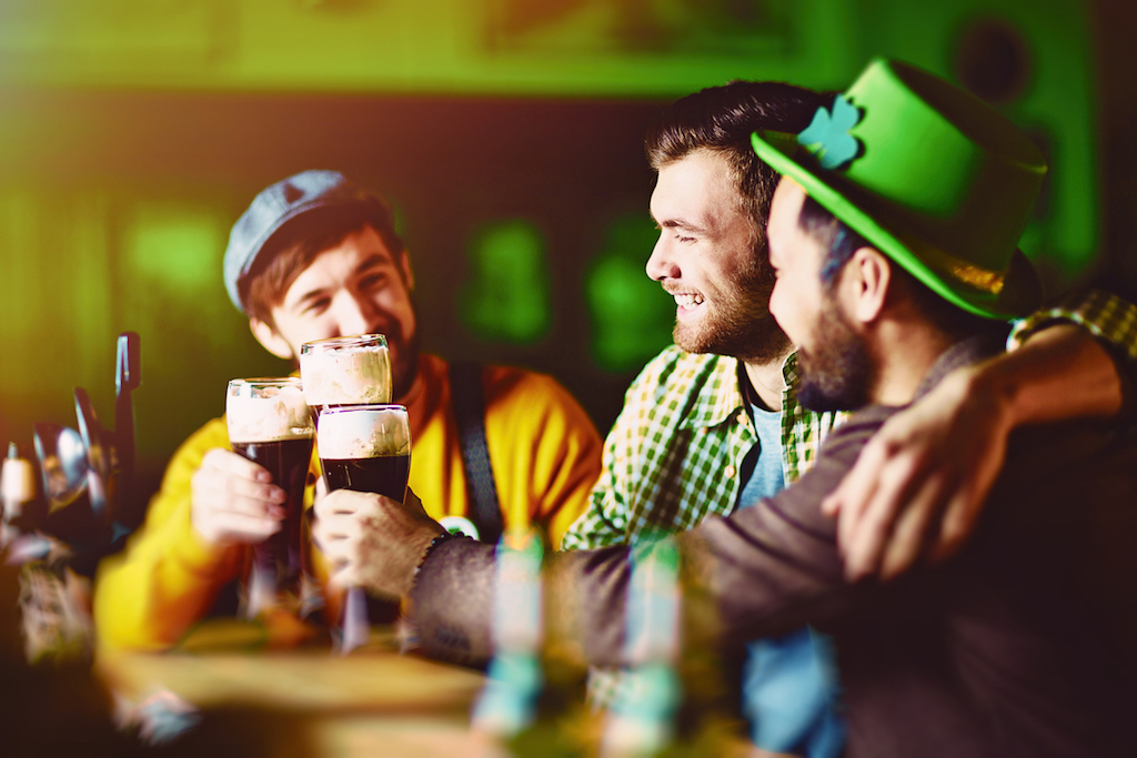 Three slightly drunk friends dressed in traditional green enjoying dark beer during meeting in Irish Pub on St. Patricks day