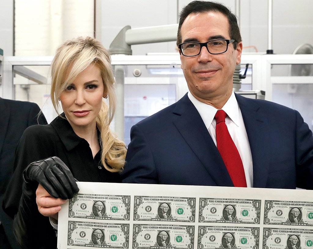 "In the year since Steven Mnuchin joined the President's Cabinet, Louise Linton has made numerous appearances at her husband's office, which some Treasury employees found ""disrespectful."" Critics pounced on this photo of the couple unveiling the new $1 bills bearing his signature. Photograph by Jacquelyn Marti/AP Images."