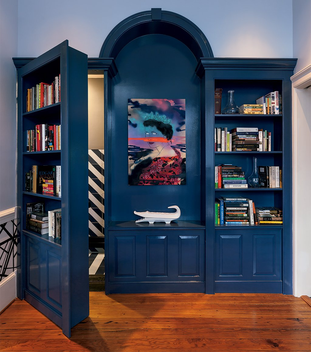 A panel of built-in shelving in the dining room doubles as a door that hides the powder room. Photograph by Mark Luthringer.
