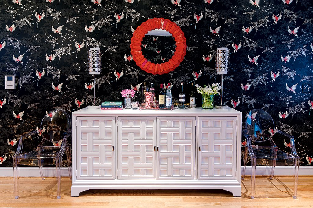 The bird-patterned wallpaper by Osborne & Little plays off the hot-pink vintage dining chairs. Photograph by John Magor.